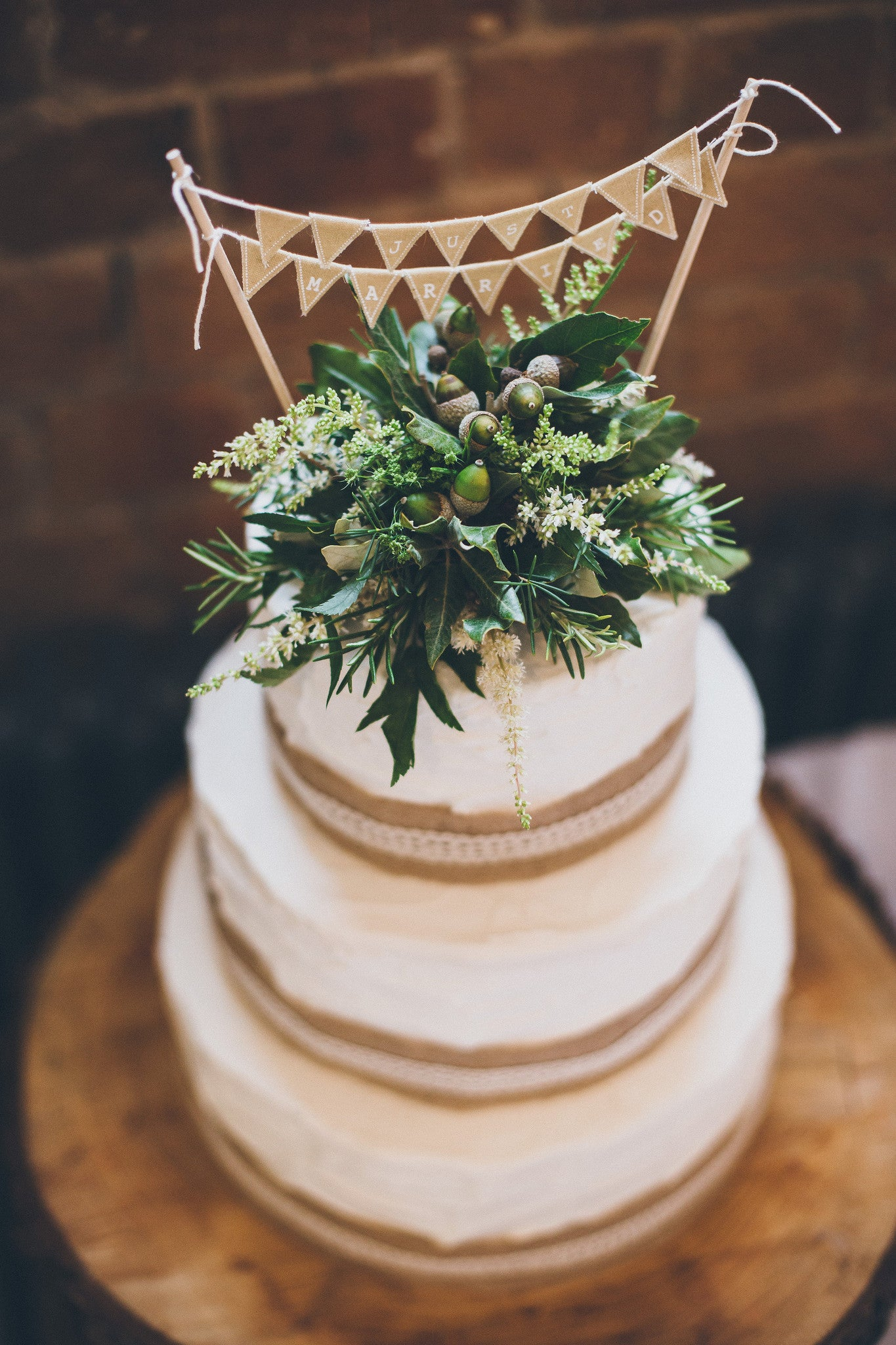 Top of a wedding cake floral design in greens and whites for a country themed wedding.