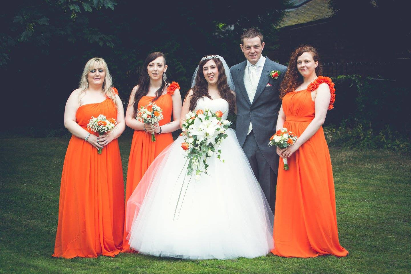 Bridal party with wedding flowers including orange Roses, white Lilies and Gypsophila.