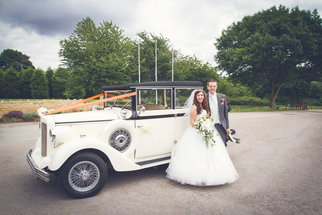 Bride and Groom with wedding car and wedding bouquet.