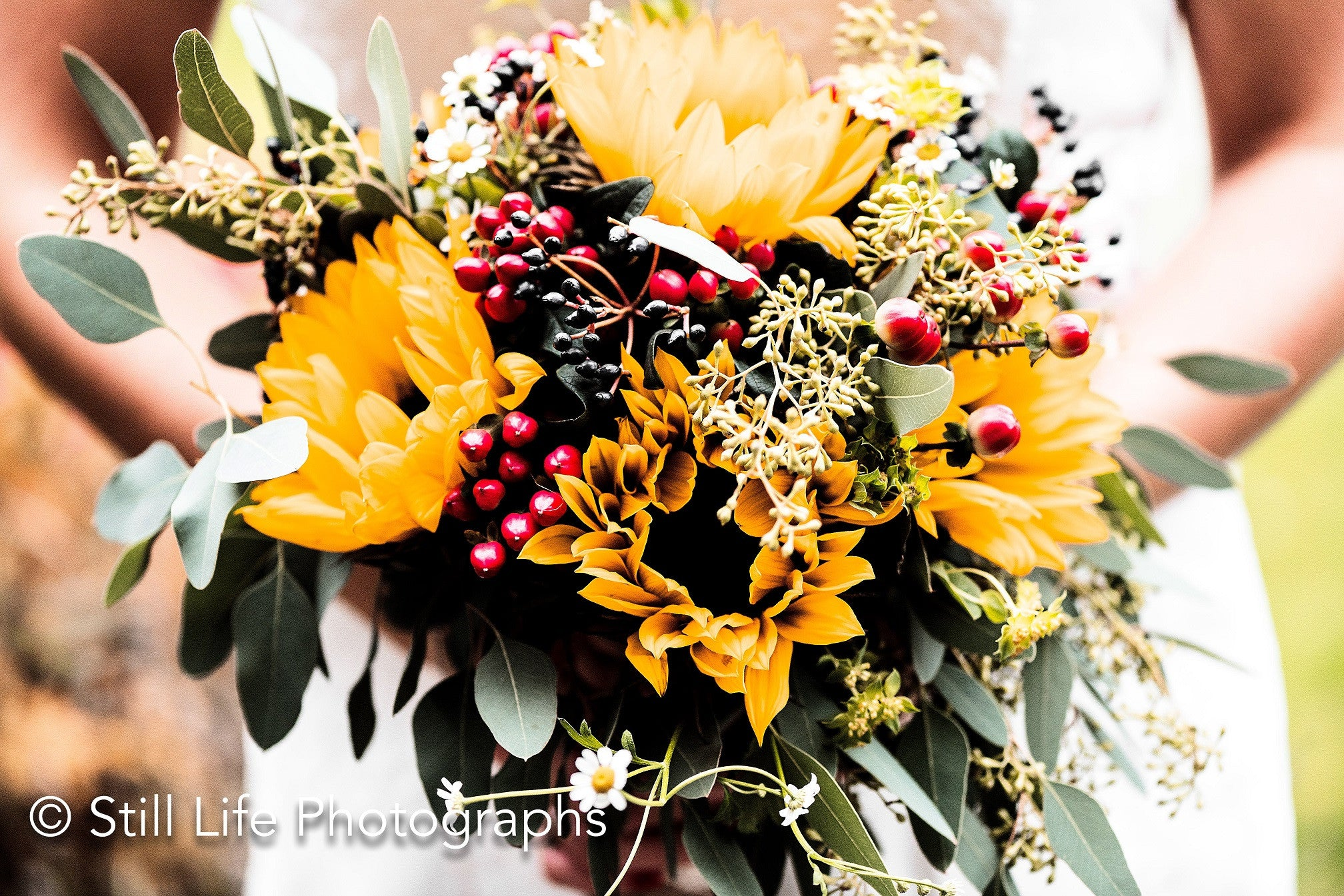 Autumnal bridal bouquet with yellow Sunflowers and red Rosehip berries.