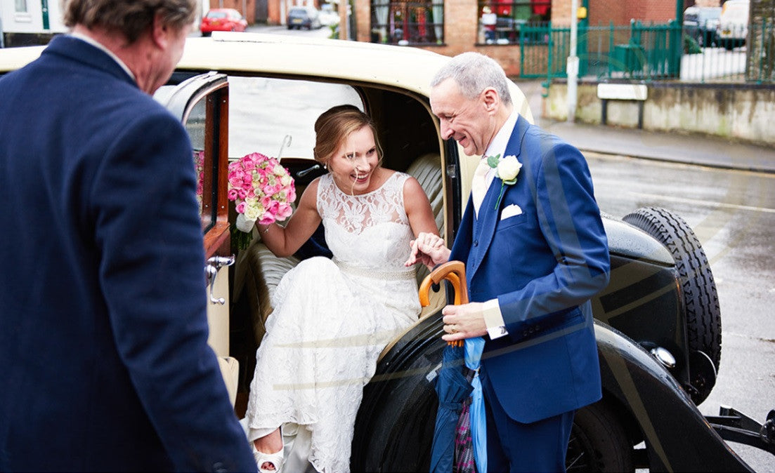 Bride in wedding car with pink Rose bridal bouquet.