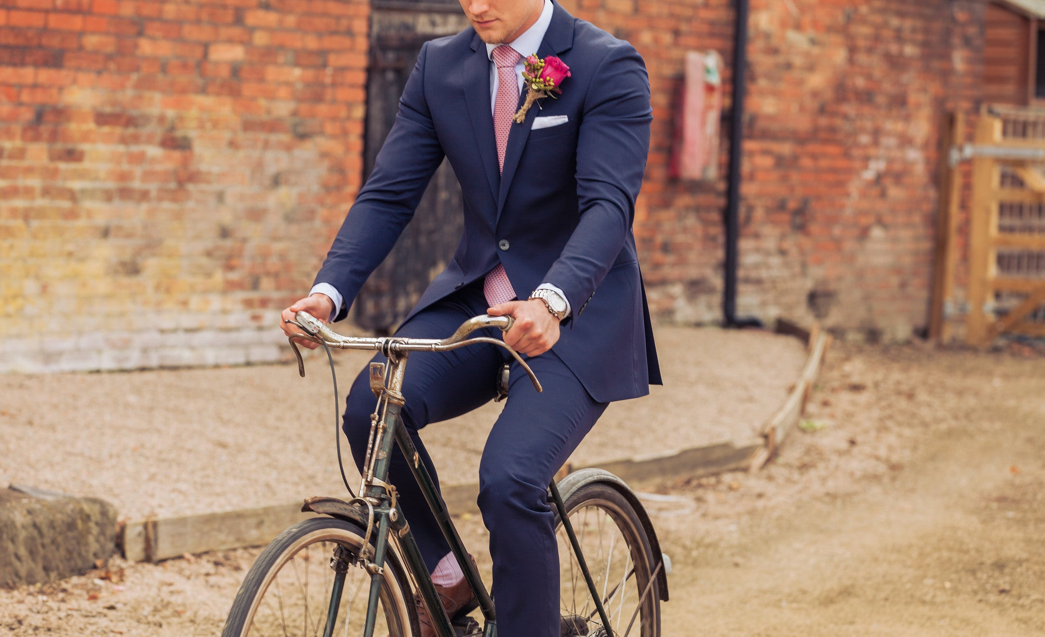 Wedding photoshoot showcasing our wedding buttonhole with the groom riding a bike.