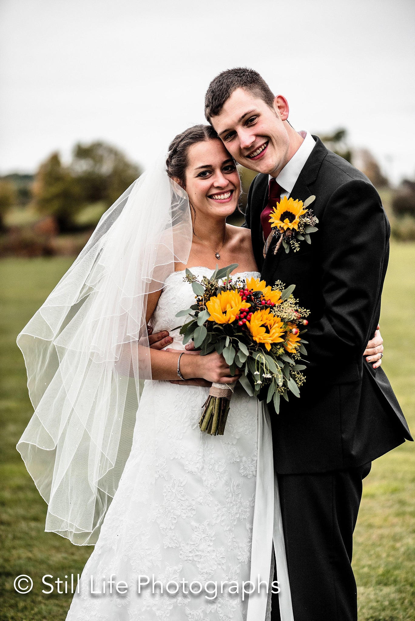 Bride and Groom with golden Sunflower and red Rosehip berry bouquet and buttonhole.