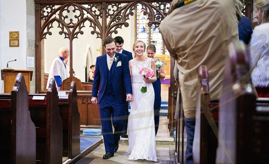 Wedding couple walking down church isle with wedding bouquet and buttonhole.