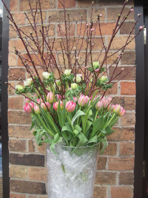Floral arrangement in large glass vase for business event, with pink tulips and large twig decorations.