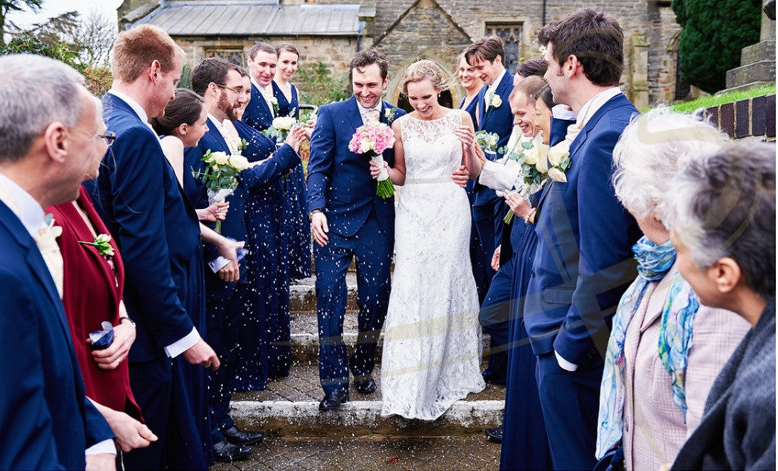 Wedding couple with confetti, holding pink Rose bouquet.
