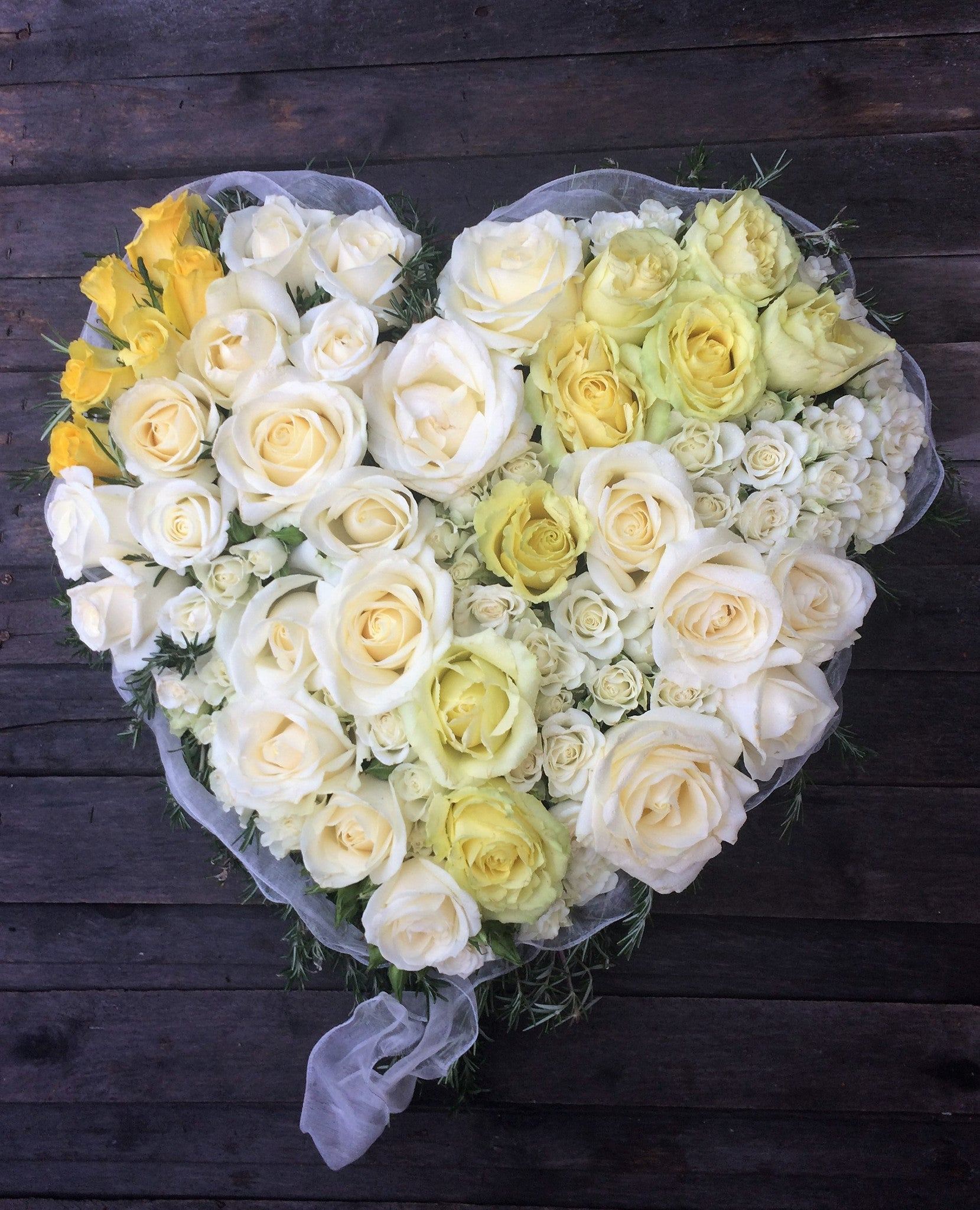 Natural style funeral heart in whites, creams and yellows with Roses.