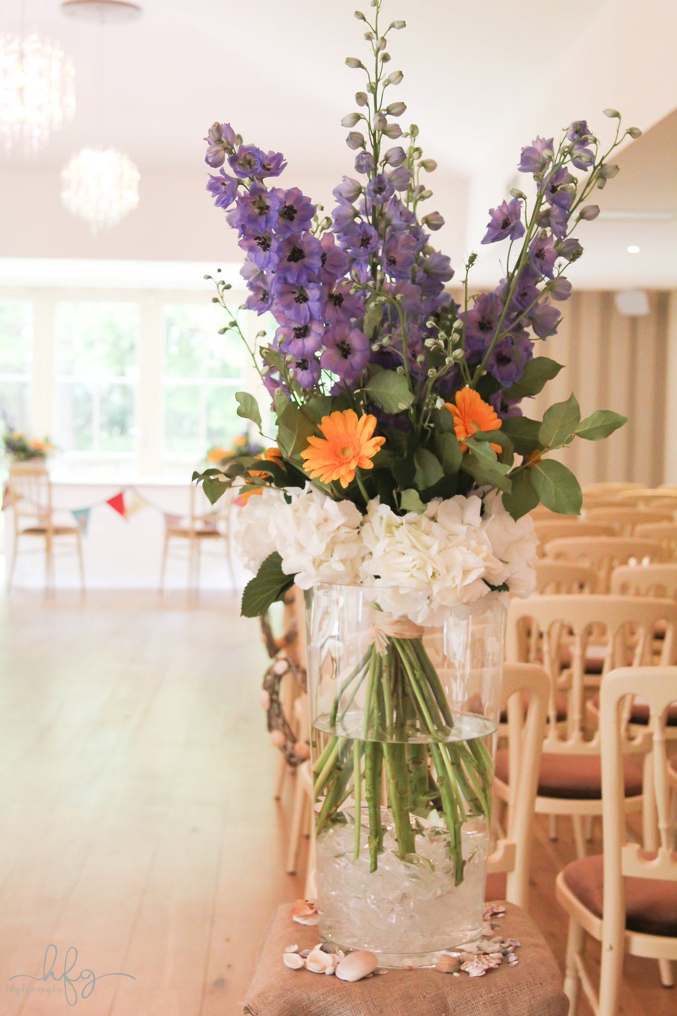 Venue decorations with orange Gerbera, purple Gladioli, white Hydrangea and foliage, fitting in with seaside theme.
