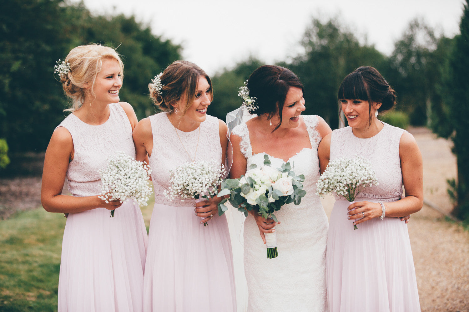 Bride and Bridesmaid's with their wedding flowers in shades of pink and white.
