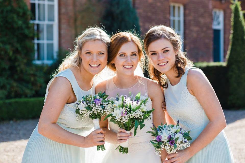 Bride with bridesmaids and their wedding flower bouquets.