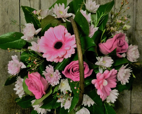 Pink basket arrangement with Gerbera, Roses, Chrysanthemums and Wax Flowers