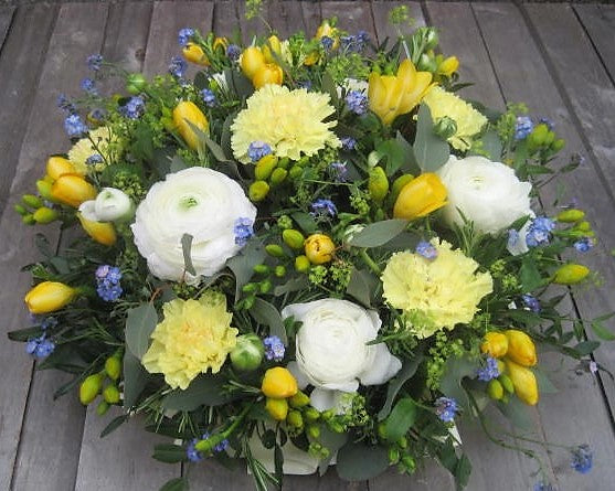 Funeral posy pad with Ranunculus, Carnations, Freesia and Forget-Me-Nots.