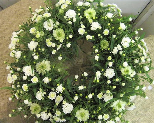 Funeral posy pad with Hydrangea, Lisianthus, Roses, Rosemary and Allium.