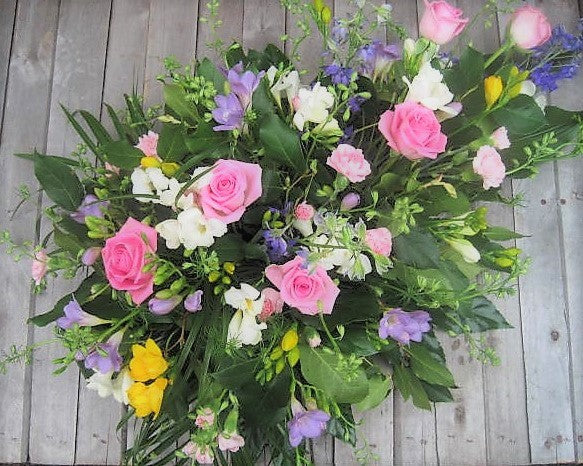 Pink and white single ended funeral spray with Roses, Freesia and Carnations.