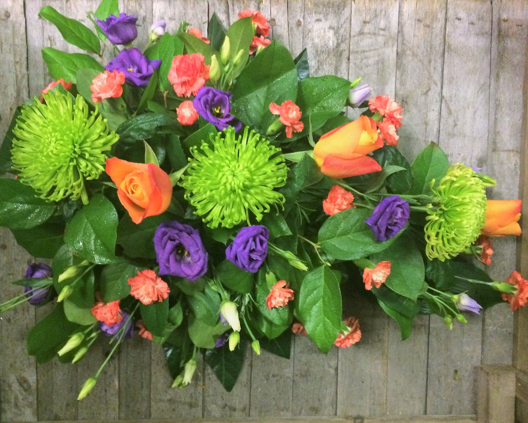 Green, orange and purple vibrant single ended funeral spray with Roses, Blooms, Lisianthus and Spray Carnations.