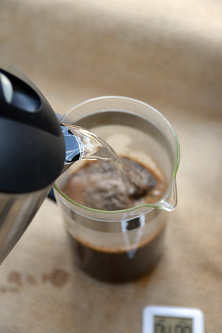 Pour hot water over coffee grounds in French press