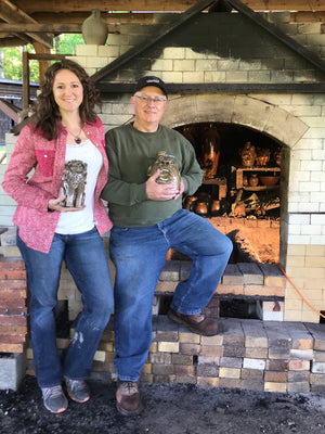 Crystal King and Father Terry King Standing with Face Jugs in front of their Wood Kiln In Seagrove NC