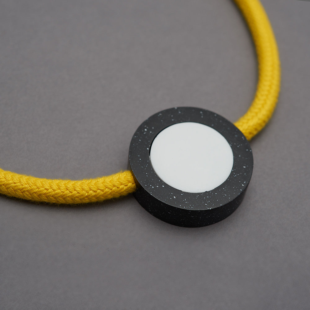 Ab necklace is a bright and striking necklace with movable resin parts. Bright yellow rope. Full drop 40cm, fully adjustable using a black ball which sits behind the neck. Black speckled resin circle 40mm diameter x 10mm White resin circle which sits inside, 30mm x 10mm Black resin rectangle 30mm x 10mm