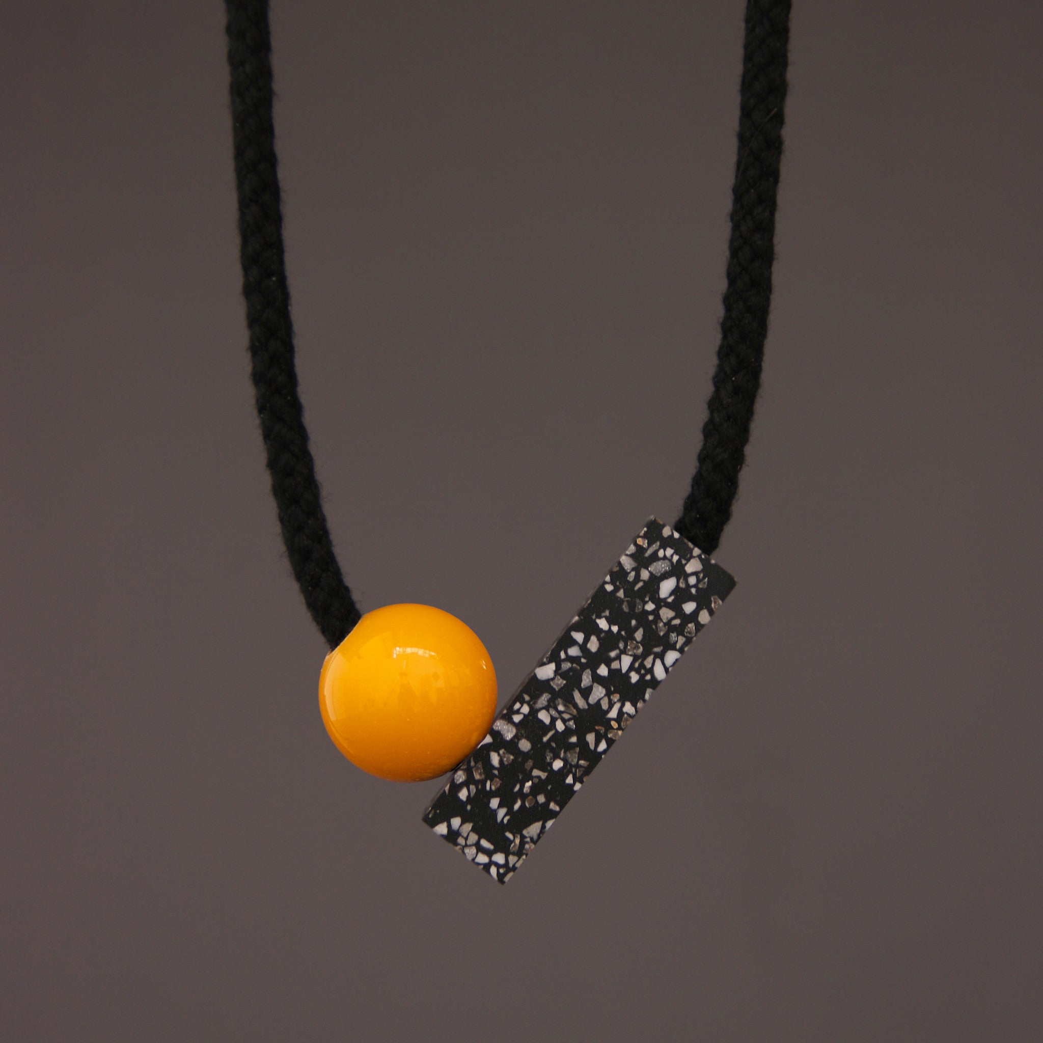 The Ad necklace is a minimalist and stylish design. It is composed of 2 main parts - A section of black corian with fine speckles of grey and white (60mm x 18mm) and a coloured ball (25mm).