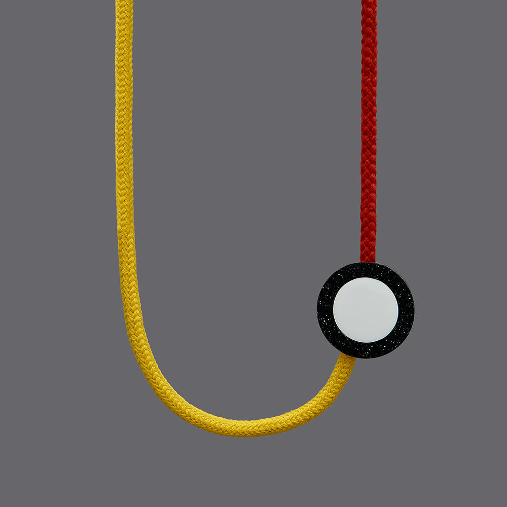 The Beck necklace is a Bright and striking statement necklace inspired by the London Underground Tube Map. Bright yellow and red rope work in combination with resin parts. Full drop 40cm, fully adjustable using a black ball which sits behind the neck.
