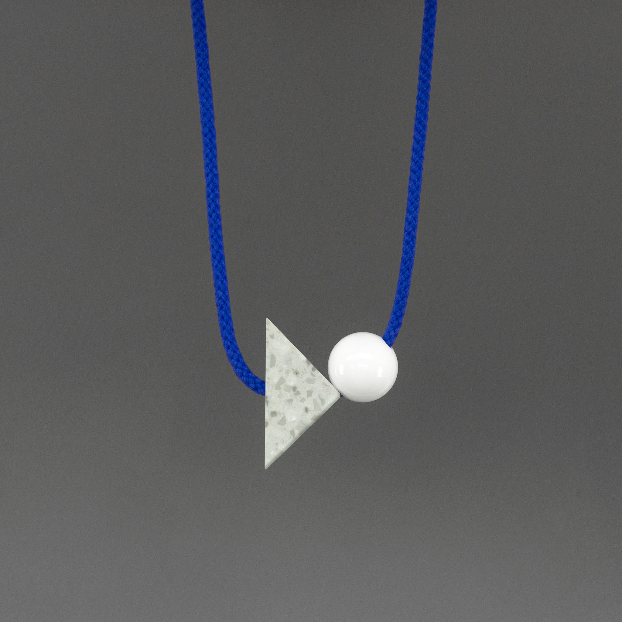 The Brandt necklace is a bright and bold statement. Stepping away from our signature black cord, Brandt's bright blue cord offers something different and looks great against a variety of tops.  An off-white triangle of corian with white and grey speckles (70mm x 50mm) and a white resin ball (30mm).