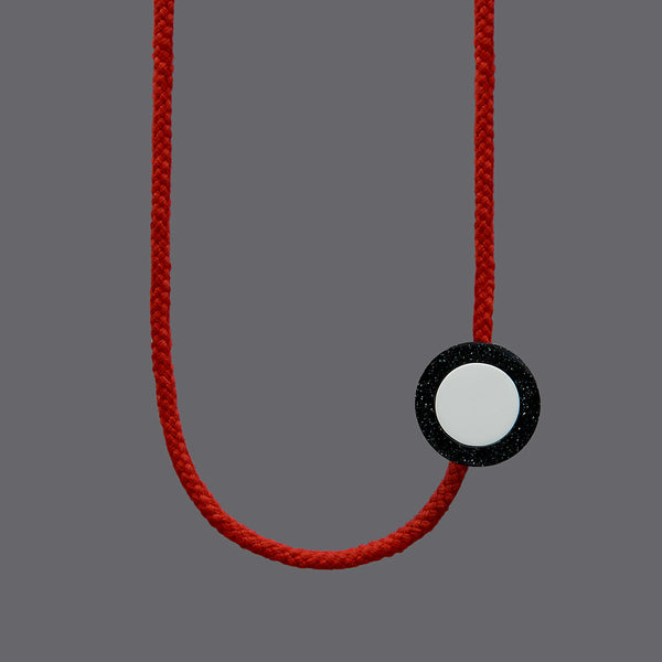 The Ed necklace is part of the collection we launched with Transport For London at Clerkenwell Design Week 2017.Bright and striking necklace. Bright red rope. Small yellow balls on the end of each rope. (15mm)Black speckled resin circle 40mm diameter x 10mm White resin circle which sits inside, 30mm x 10mm