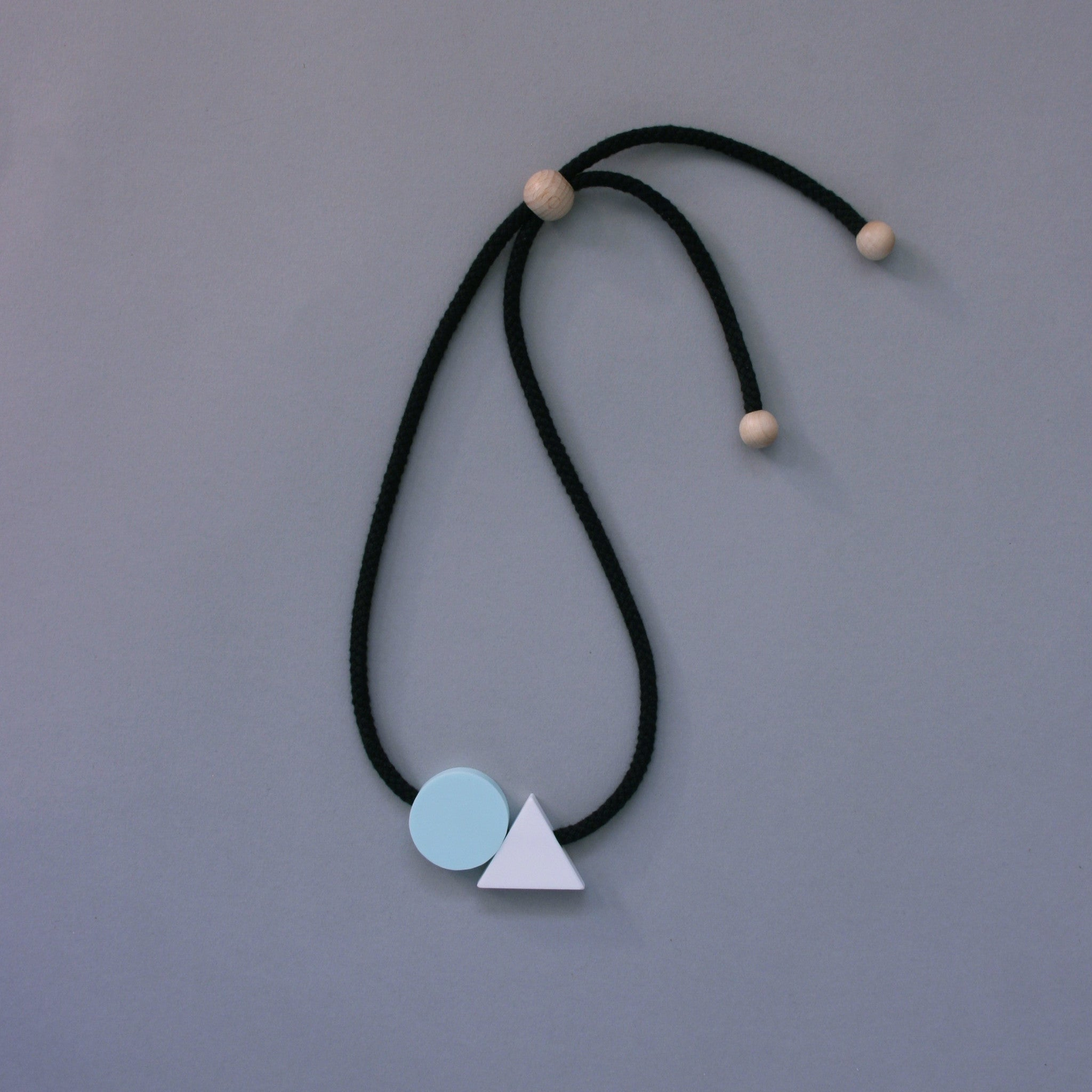 The Ellsworth necklace is a pleasing balance of 2 geometric shapes. A mint circle sits neatly beside a white triangle offering a striking and minimal addition to any outfit. A geometric statement necklace.
