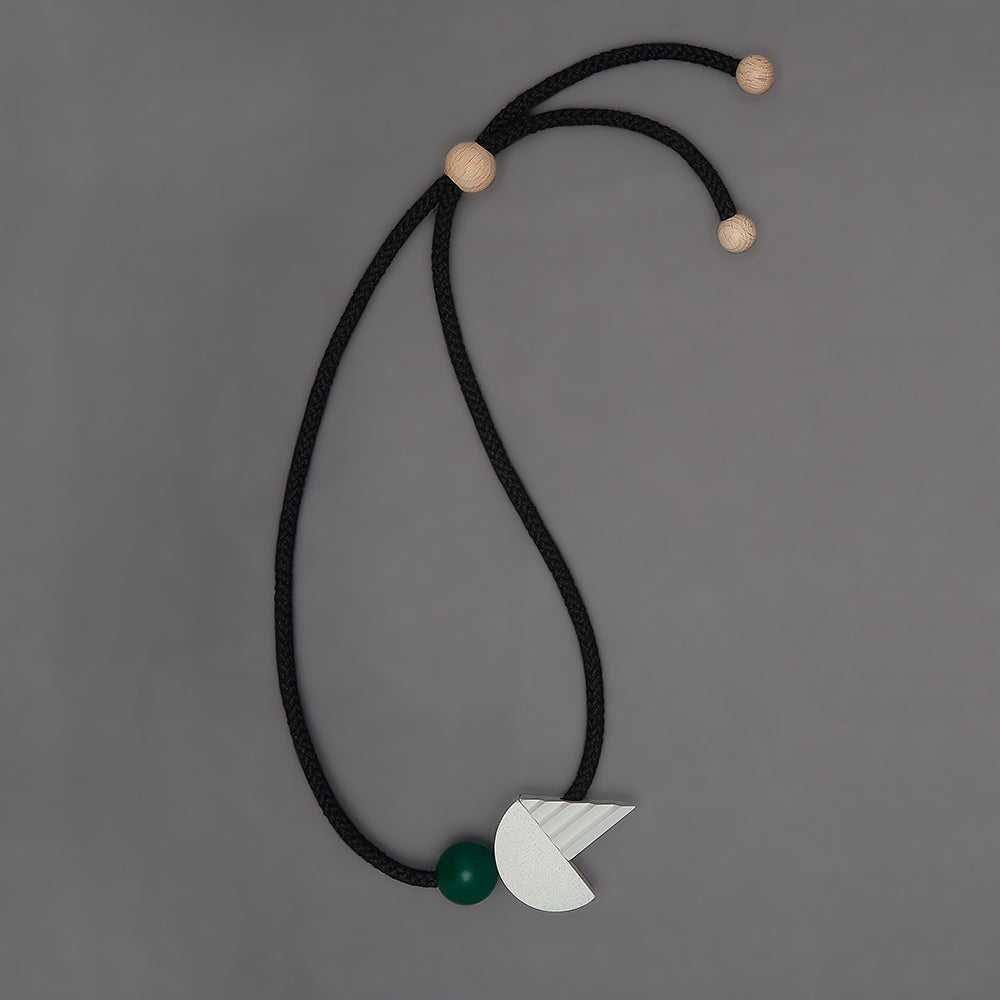 The pop necklace is composed of 2 handcast shapes. A lovely concrete-effect curve measuring 50mm x 25mm which sits beside a cast ridged triangle which measures 30mm x 45mm. The bright green ball (25mm) offers a pop of colour beside the understated concrete resin shapes.