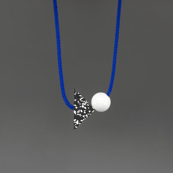 The Ilya necklace is a bright and bold statement. Stepping away from our signature black cord, Ilya's bright blue cord offers something different and looks great against a variety of tops. Illya is composed of 2 main parts - a black triangle with white speckles (70mm x 50mm) and a white resin ball (30mm).