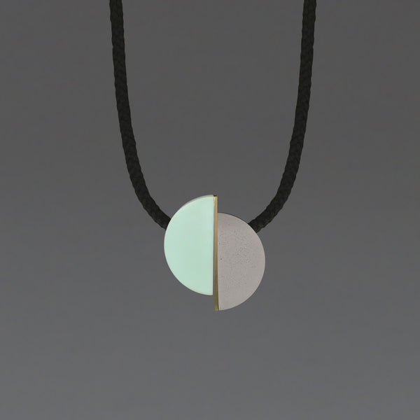 The Klee necklace is both elegant and fun. The three sections can move freely allowing the design to fall in different ways.  Klee is composed of our hand cast concrete-resin, a brass strip and a mint resin curve. A playful, contemporary design.