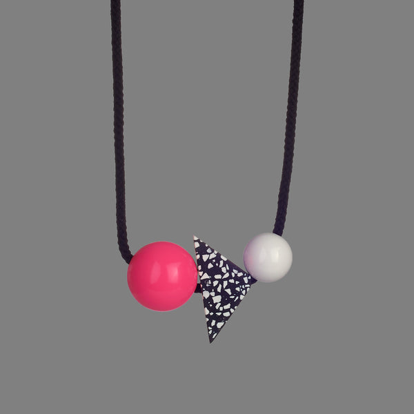 The Lina necklace is a statement necklace - bold and striking. It is composed of 3 parts - a bright pink resin ball (38mm), a triangle of black resin with white chips (70mm x 50mm) and a white resin ball (30mm). Black cord full drop 45cm.