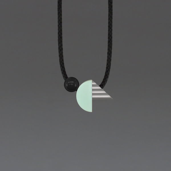 Striking geometric necklace composed of a mint resin curve and a hand cast ridged concrete-look resin triangle. The unusual mix of materials creates an intriguing necklace of varying textures and shapes.