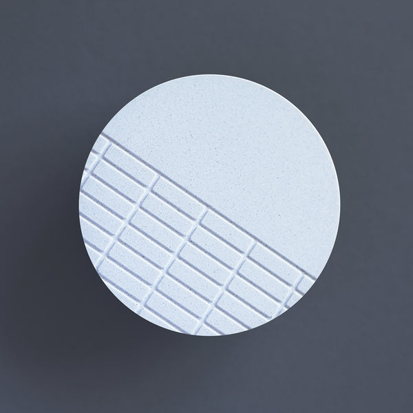 Handcast brooch inspired by the brutalist architecture of London's Barbican centre. This circular brooch has a fine grid recessed over half of the surface. Each brooch is cast by hand in our south London studio and comes in branded gift box. (7cm diameter)
