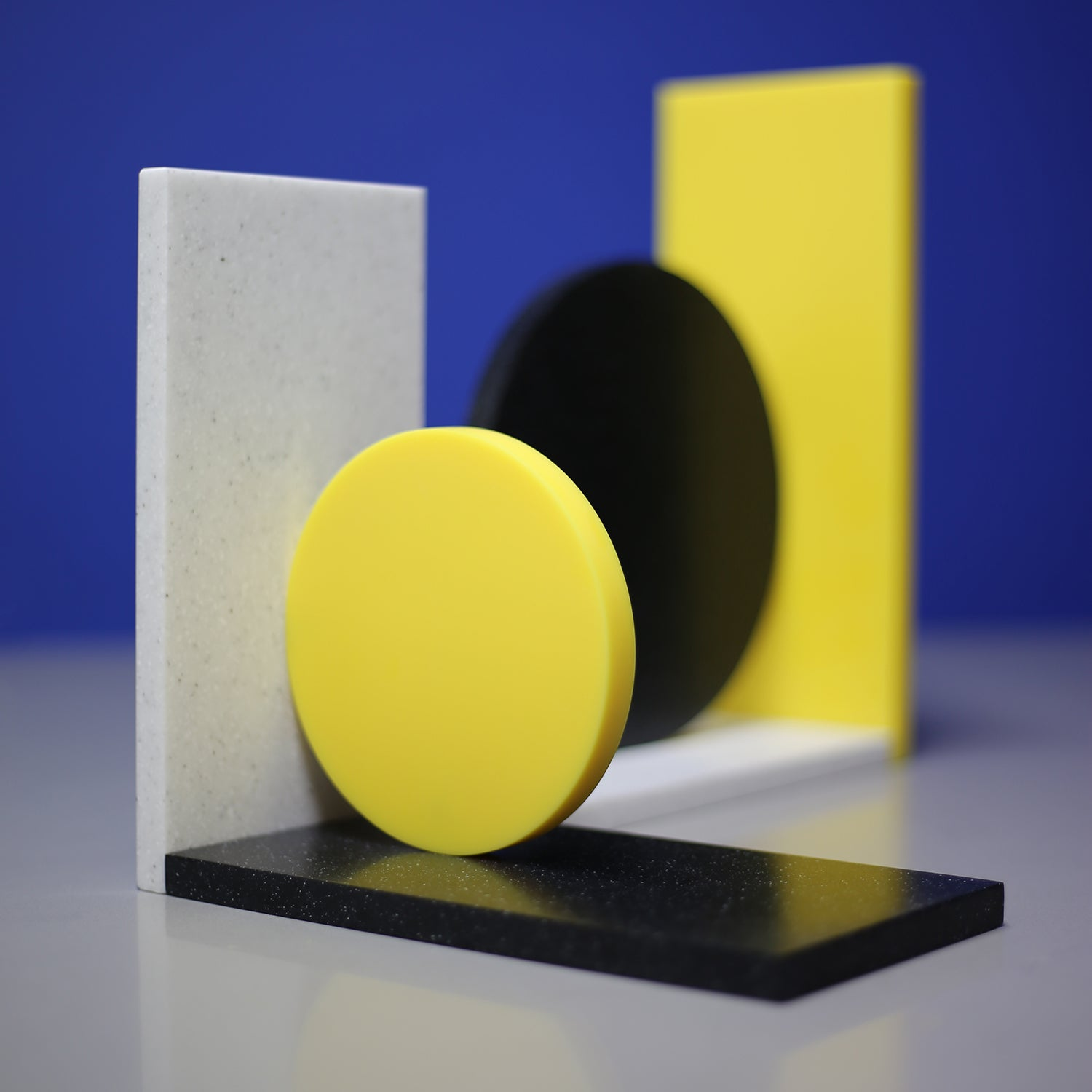 Corian Dot Bookends made to order. Asymmetrical design makes each end different. Yellow corian, black speckled corian, light grey speckled corian.  A colourful addition to any shelf!