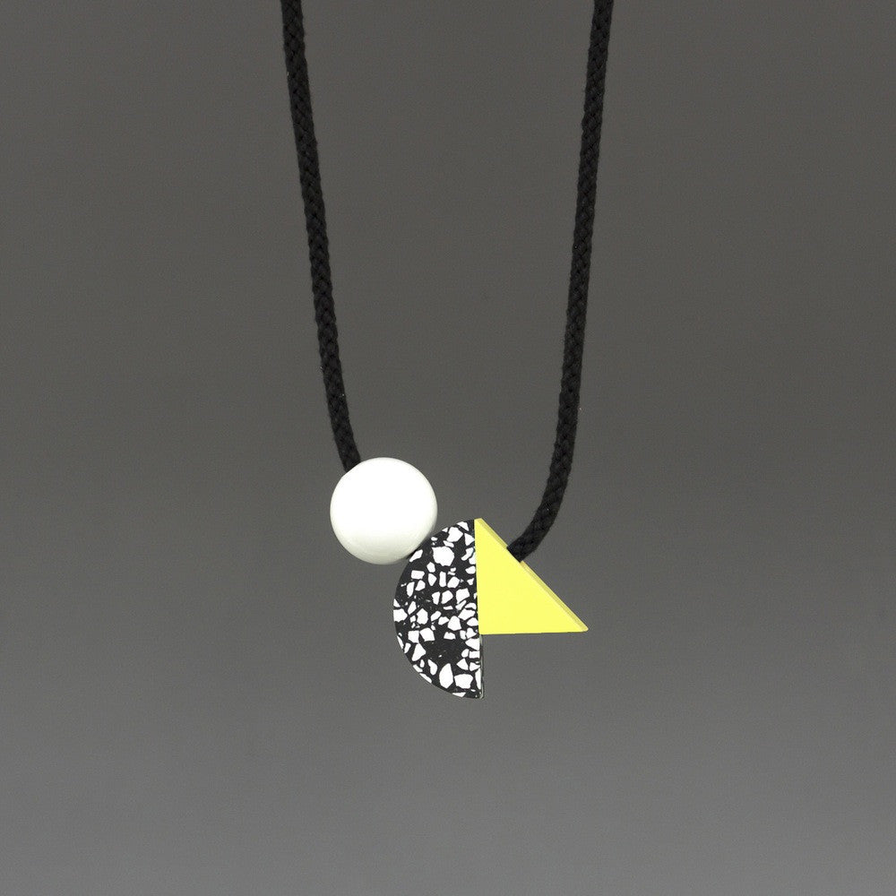 Ella is a bold necklace composed of 3 geometric shapes on black cord. Black and white speckled curve, yellow triangle and white ball. Handmade in our London studio. A contemporary statement necklace.