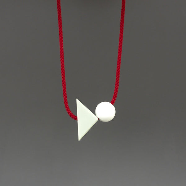 Bold, simple and playful necklace. Looks great on a simple top. Pale green corian triangle on a bright red cord with a resin ball. Geometric contemporary necklace.