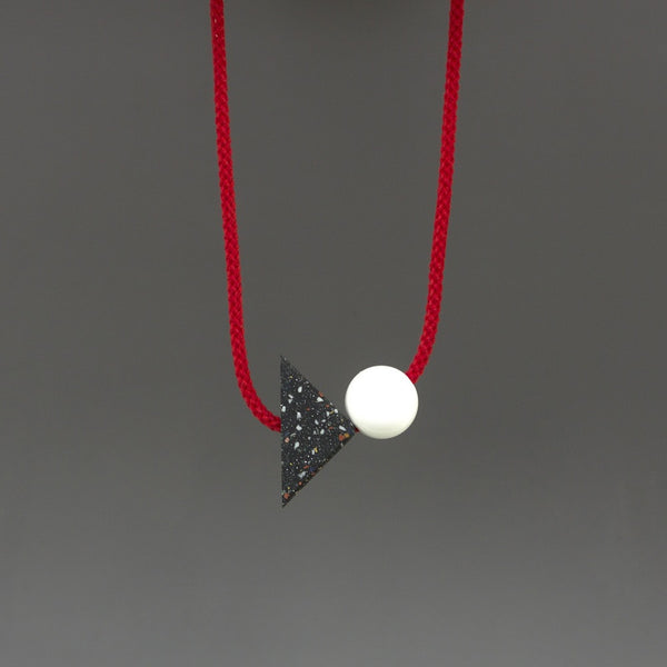 Konstantin is a bold and striking geometric necklace composed of resin parts on bright red cord. Resin triangle is black with little coloured speckles. Measures 70 x 50mm  Necklace can be worn high at neck length or as a longer pendant due to adjustable cord.Full drop is 45cm Handmade in our London studio.