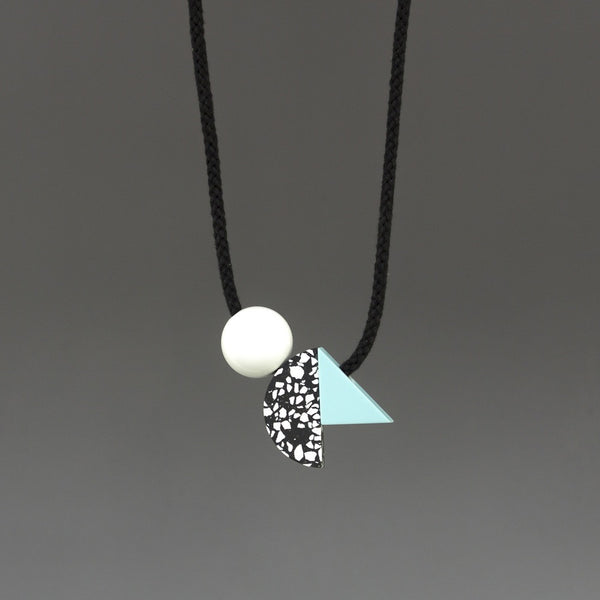 Bold and striking necklace composed of 3 geometric shapes on black cord. A handcast black and white curve sits between a shiny white ball and pale blue resin triangle. Handmade in London studio.