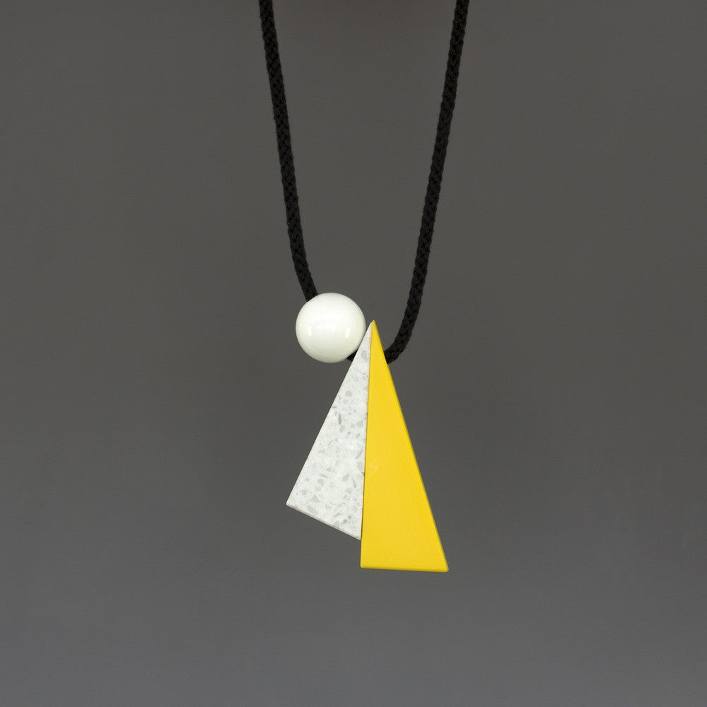 Hannes is a striking geometric necklace composed of 3 geometric shapes - 2 long triangles in yellow and marbled white and a resin ball. Necklace can be worn at varying lengths due to the wooden ball behind the neck which can be moved up & down to adapt necklace height.