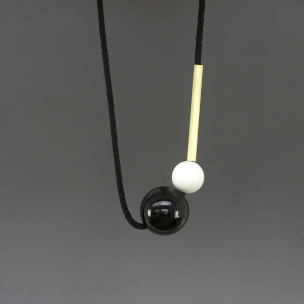 Minimal necklace design by London design studio One We Made Earlier. Black and white resin balls and a brass tube. Necklace is fully adjustable. Contemporary design.
