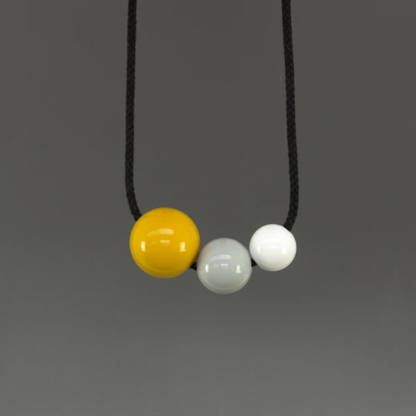 Bold, striking and fun statement necklace composed of three bright resin balls. Yellow, grey and white shiny resin balls on black cord.