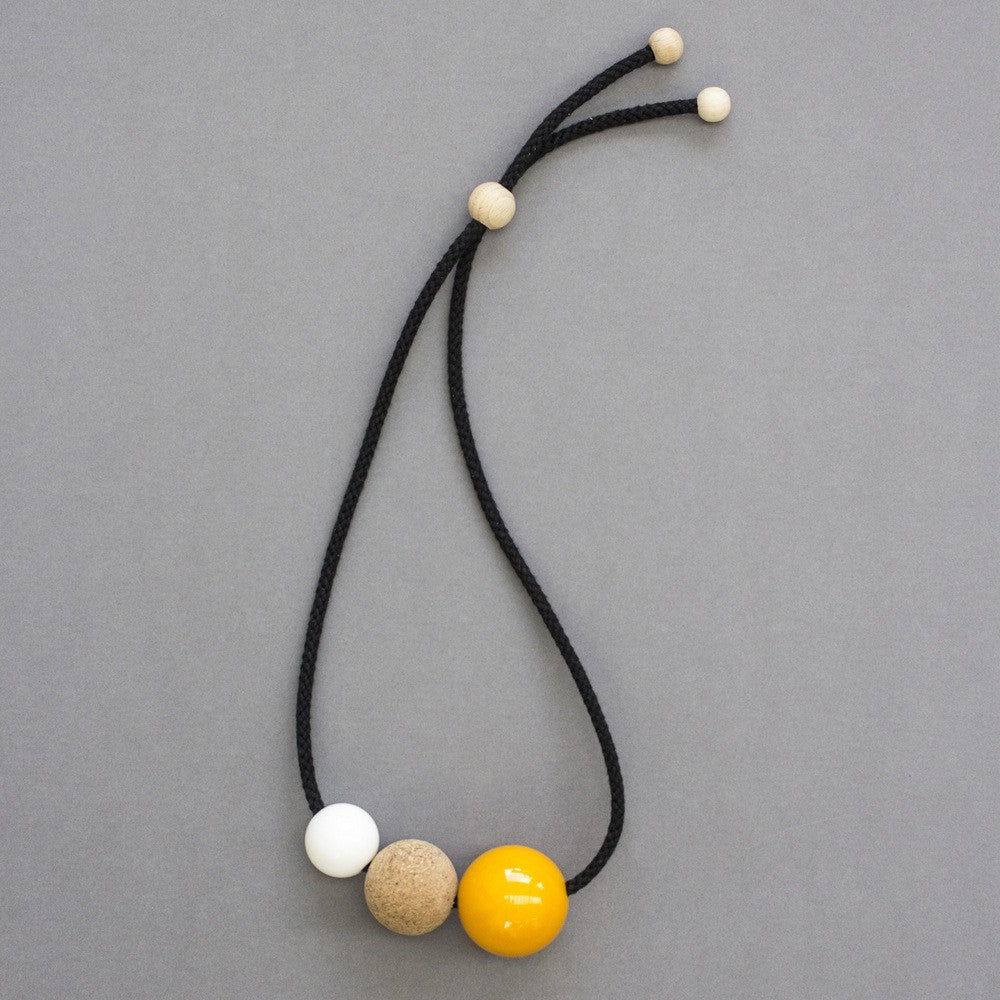 Bright and bold necklace composed of pink and white resin balls and cork on a black cord. Necklace can be worn either at neck or pendant length due to adjustable cord. Full drop is 45cm. This statement necklace looks great on a simple top. Handmade in our London studio.
