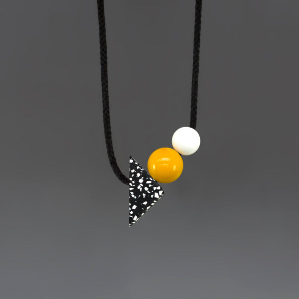 Otto is a statement necklace by London design brand One We Made Earlier. Hnad cast Jesmonite triangle and bright resin balls. Modern design, geometric shapes.