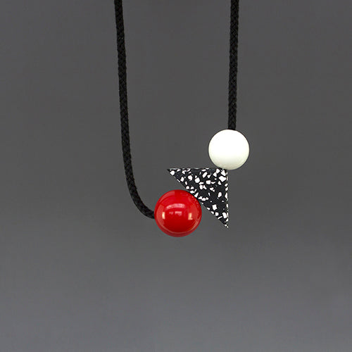 Teo is a bold and striking accessory, handmade in our London studio.  Composed of red and white resin balls with a black and white speckled jesmonite triangle.  A contemporary accessory with geometric shapes.
