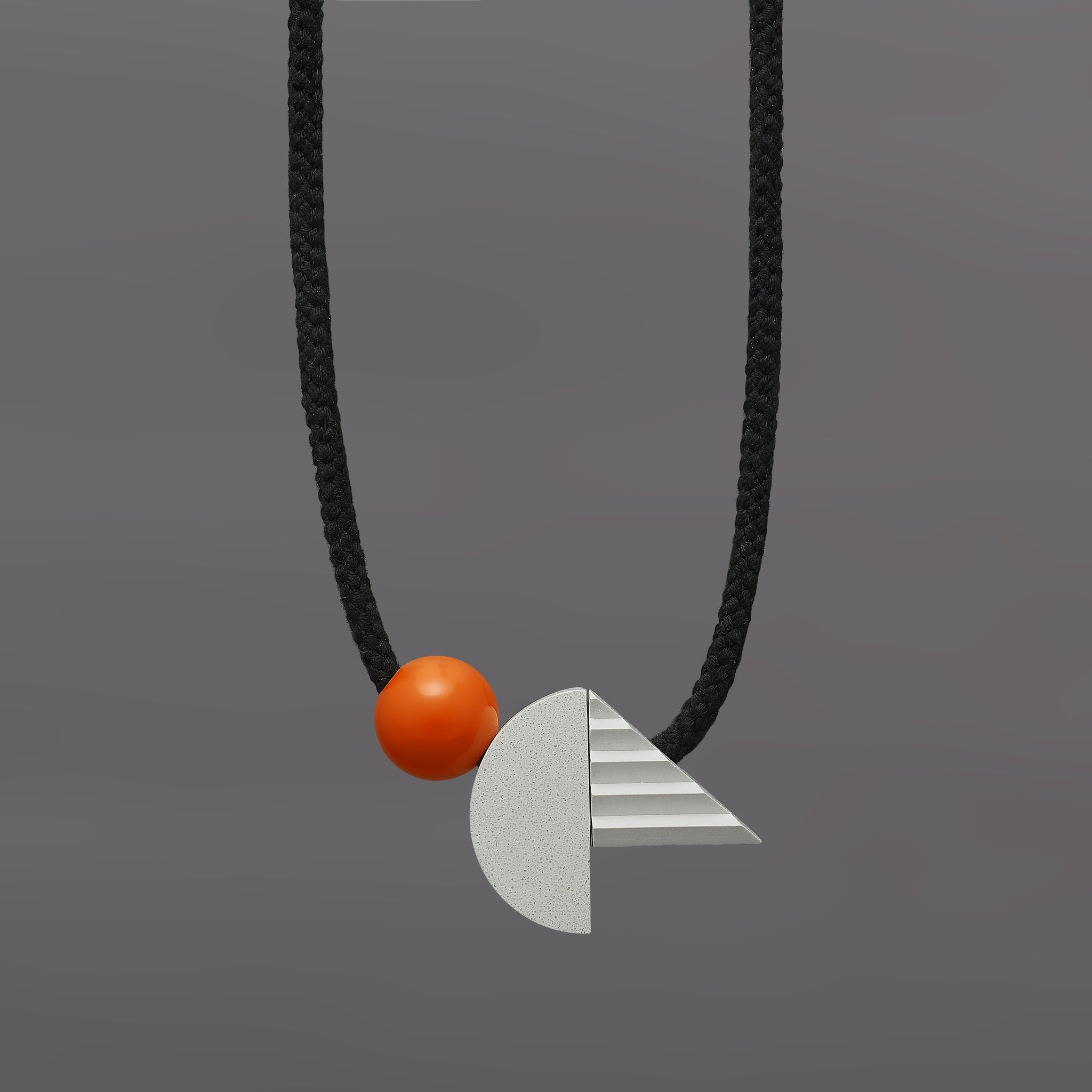 The pop necklace is composed of 2 handcast shapes. A lovely concrete-effect curve measuring 50mm x 25mm which sits beside a cast ridged triangle which measures 30mm x 45mm. The bright orange ball (25mm) offers a pop of colour beside the understated concrete resin shapes.