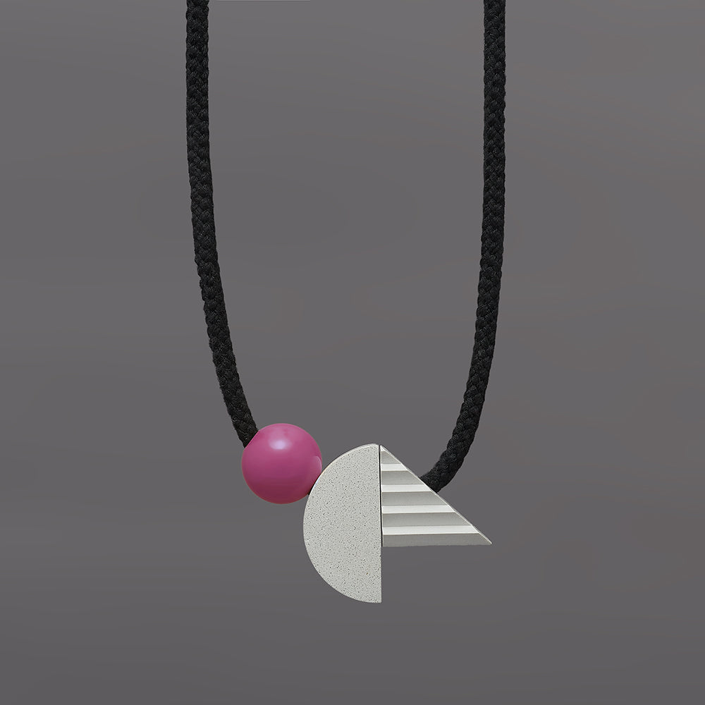 The pop necklace is composed of 2 handcast shapes. A lovely concrete-effect curve measuring 50mm x 25mm which sits beside a cast ridged triangle which measures 30mm x 45mm. The bright pink ball (25mm) offers a pop of colour beside the understated concrete resin shapes.