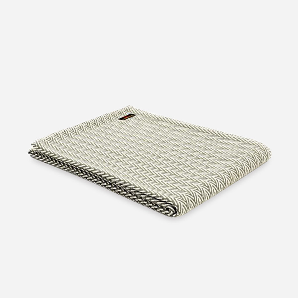 A olive green and white blanket, made from organic cotton, it features a herringbone pattern. Buy online or shop in store at Jo & Co home, North Cornwall, UK