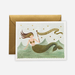 A watercolour birthday card featuring an illustrated mermaid playing amongst the waves, with metallic gold foil details, and the words 'Happy Birthday' in gold.