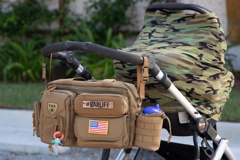 Diaper bag hanging from stroller with stroller straps and baby seat with camo milks snob cover