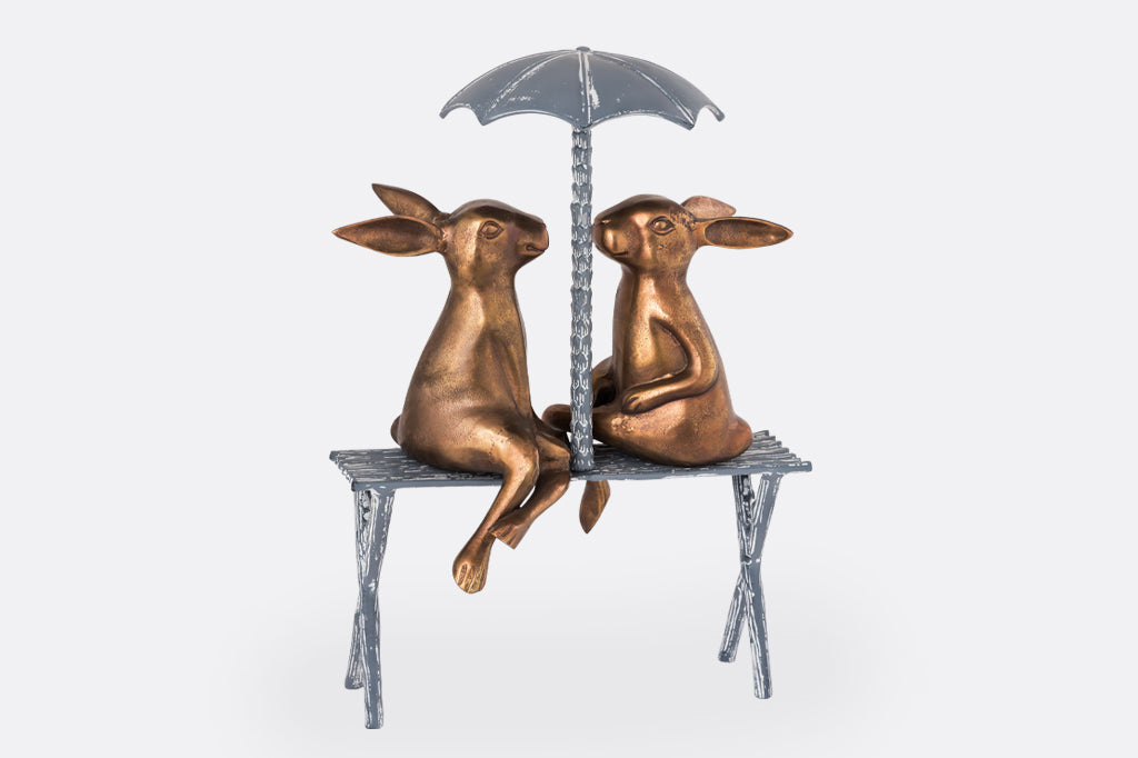 Two Rabbits sit on a bench under an umbrella